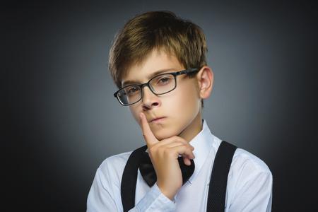 desconfianza: duda, la expresión y el concepto de la gente - pensamiento del muchacho sobre fondo gris. Foto de archivo