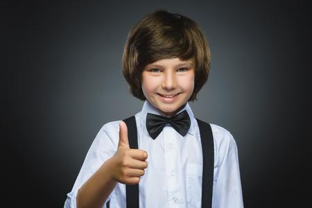 percepción: aislado Retrato de detalle exitosa niño feliz fondo gris. expresión de la emoción rostro humano positivo. percepción de la vida visión logro.