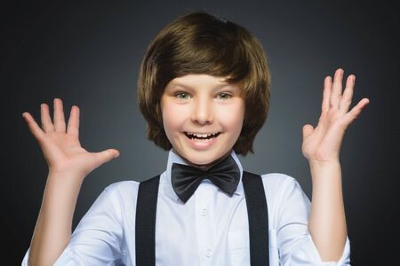 suddenness: Closeup Portrait of happy boy going surprise isolated on gray background. Stock Photo