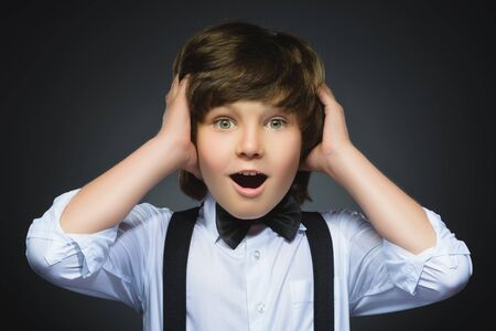 wonderment: Closeup Portrait of happy boy going surprise isolated on gray background. Stock Photo
