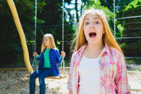 Portrait of screaming child at park. On the background other girl riding a swing.