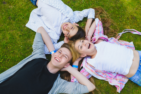 fantasize: Smiling kids having fun at grass. Children playing outdoors in summer. teenagers communicate outdoor.