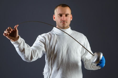 informal clothing: Fencing athlete posing with a sword or epee on gray background. Stock Photo