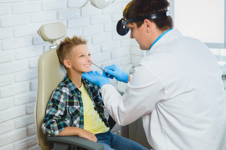 general pediatrician: Ent doctor or Otolaryngologist examining a kid nose.