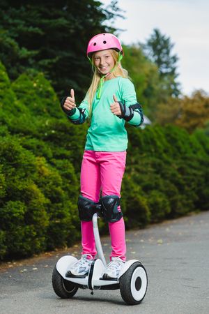 Happy girl standing on hoverboard or gyroscooter outdoor. Zdjęcie Seryjne