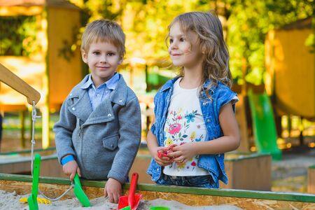 citypark: group of happy children playing in sandbox at playground.