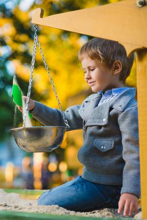 citypark: happy little boy playing in sandbox at playground.