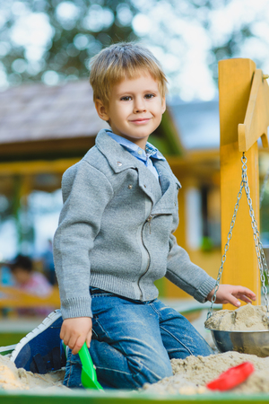 happy little boy playing in sandbox at playground.