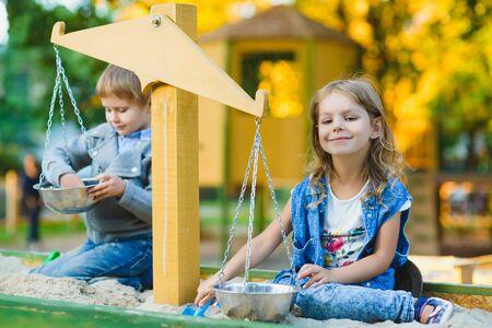 group of happy children playing in sandbox at playground.