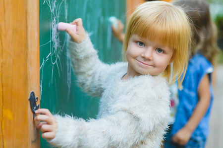 desk toy: Cute children drawing with chalk on blackboard outdoor.