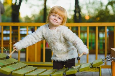 xilofono: Cerca retrato de niña linda que juega al aire libre xilófono.