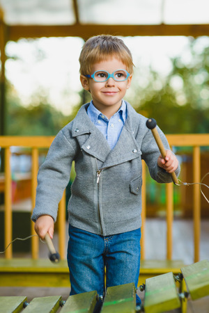 Close up portrait of cute boy playing xylophone outdoor.