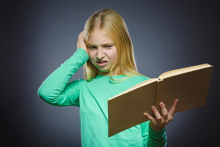ocd: angry or stressed girl with book. Closeup Portrait of handsome teen on grey background. studies concept. Stock Photo