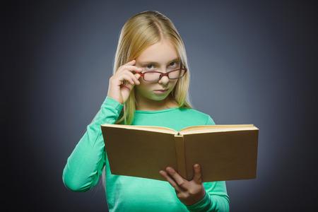 ocd: wondering girl with book. Closeup Portrait of handsome teen on grey background. studies concept.