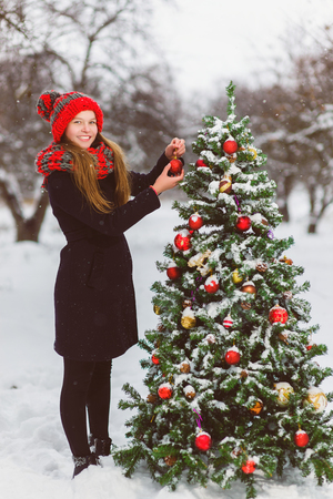 Cute teenager or girl decorating christmas tree outdoor