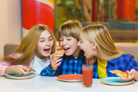 smiling boy and girls eating pizza or drinking juice indoor Zdjęcie Seryjne