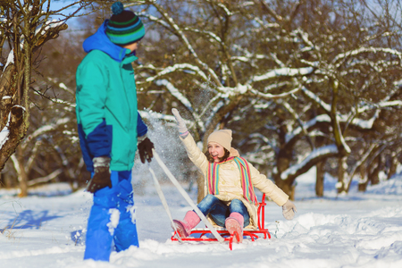 Happy boy and girl sledding in winter outdoor Stock Photo