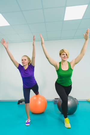 Two young sporty women doing gymnastic exercises or exercising in fitness class Stock Photo
