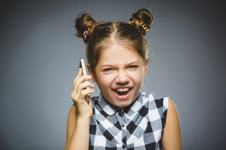 Portrait of offense girl with mobile or cell phone. Negative human emotion