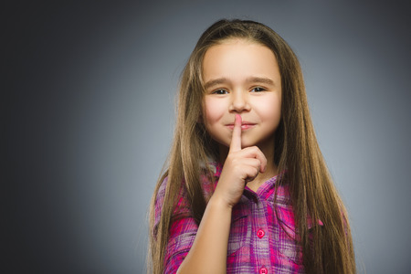 girl placing finger on lips asking shh, quiet, silence on gray background
