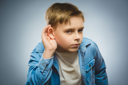 Curious Disappointed boy listens. child hearing something, hand to ear gesture