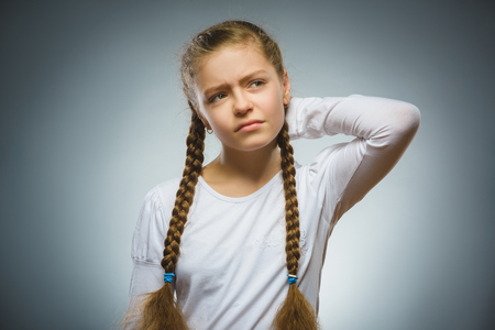 musing: Closeup Thoughtful girl with Hand at head isolated on Gray Stock Photo