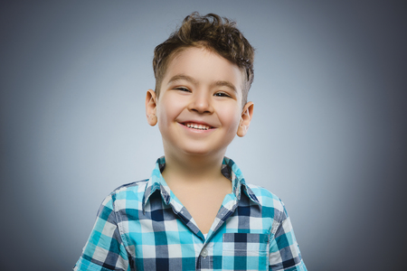 Happy child. Portrait of handsome boy smiling isolated on grey background