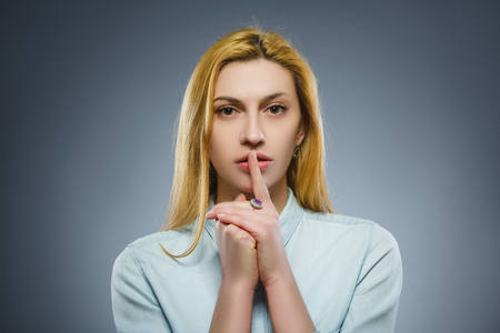 inpatient: woman placing finger on lips asking shh, quiet, silence on gray background
