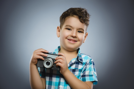 old photograph: child taking a picture using a retro rangefinder camera isolated grey background Stock Photo