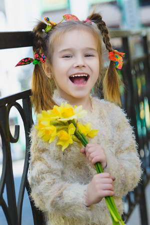 Beautiful little girl posing with a large bouquet of flowers