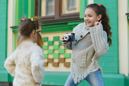 Girls posing and photographing on a retro camera in the city