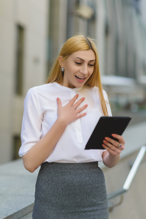 topicality: Happy business woman using tablet pc in front of office building