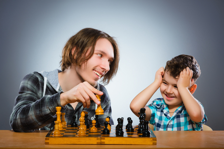 Two boys or brothers playing chess isolated on gray background