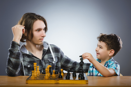chess board: Two boys or brothers playing chess isolated on gray background Stock Photo