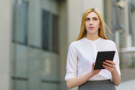 serious businesswoman using tablet pc in front of office building