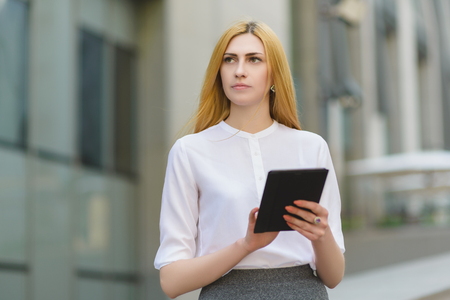 topicality: serious businesswoman using tablet pc in front of office building