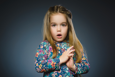 Closeup Portrait of little girl going surprise on gray background