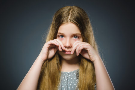 offense crying girl isolated on gray background Stock Photo