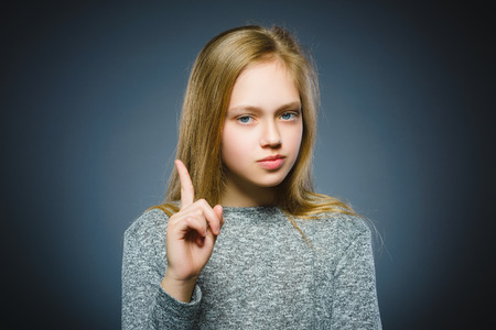 displeased and contemptuous girl with threatens finger on gray background