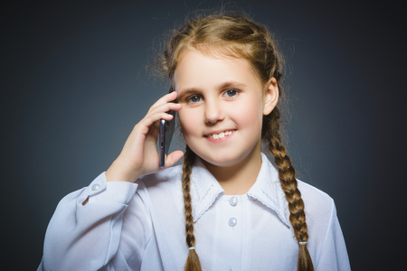 Happy cute girl with cell phone. isolated on gray