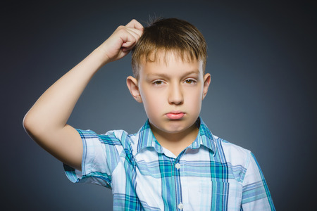 desconfianza: doubt, expression and people concept - boy thinking over gray background