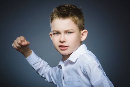 angry boy isolated on gray background. He raised his fists to strike. Closeup