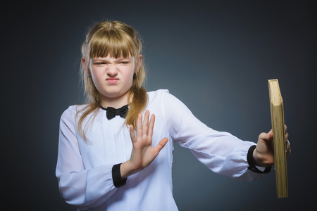 ocd: angry or stressed girl with book. child on grey background. studies concept Stock Photo