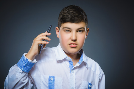 Portrait of offense boy with mobile or cell phone. Negative human emotion Stock Photo