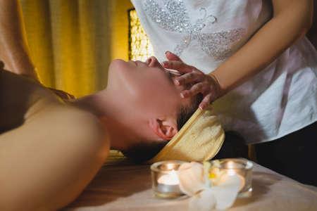 Massage therapist massaging beautiful brunette Stock Photo