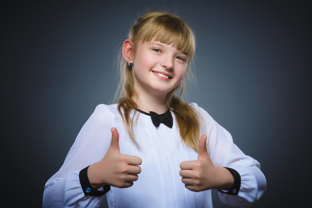 Happy girl showing thubs up. Closeup Portrait child smiling isolated on grey Stock Photo