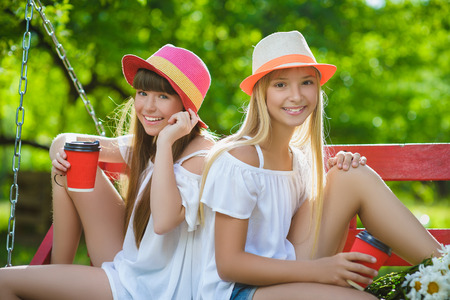 Joyful girlfriends having fun on swing outdoor. Friendship concept Stock Photo