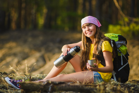 Teen girl with backpack resting on sand. Travel and tourism concept