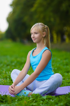 Girl doing gymnastic exercises or exercising outdoor Stock Photo