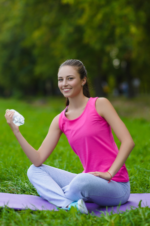Beautiful fitness athlete woman resting drinking water outdoor